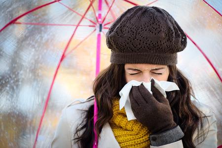 chory: Kobieta z przeziębienia lub grypy kaszel i dmuchanie jej nos chusteczką pod jesiennym deszczu. Brunetka kobieta kichanie i sobie ciepłe ubrania.