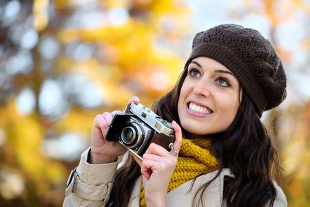 fashion photos: Fashionable happy woman taking photos with retro film camera in autumn season. Female beautiful photographer enjoying and having fun. Fashion girl wearing warm clothes.