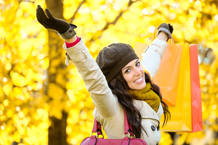 outstretching: Blissful woman raising shopping bags  and arms while having fun buying in autumn. Successful female shopper outside in fall season.