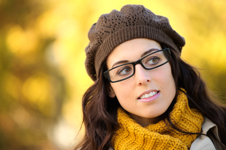 Cheerful fashion woman in autumn wearing glasses glasses, scarf and wool cap. Brunette beautiful lady with eye wear.