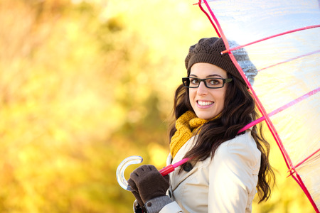 beautiful umbrella: Fashionable woman holding umbrella on rainy cold autunm day. Fashion brunette wearing glasses and warm clothes on yellow autumnal background. Stock Photo