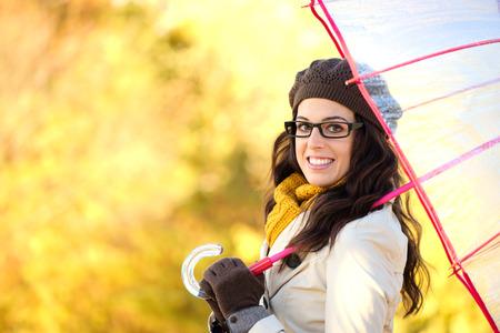 warm clothes: Moda donna azienda ombrello il giorno piovoso autunm freddo. Bruna moda indossando occhiali e vestiti caldi su sfondo giallo autunnale. Archivio Fotografico