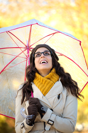 blissful: Blissful woman with glasses holding umbrella under the rain in a cold autunm day. Fashion brunette laughing and looking up.