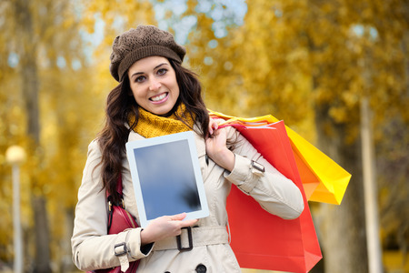 Joyful fashion woman showing digital tablet screen and holding shopping bags in autumn. photo
