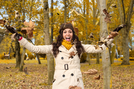 Joyful woman playing with autumn leaves and having fun in city park. Successful caucasian brunette enjoying fall season and laughing.
