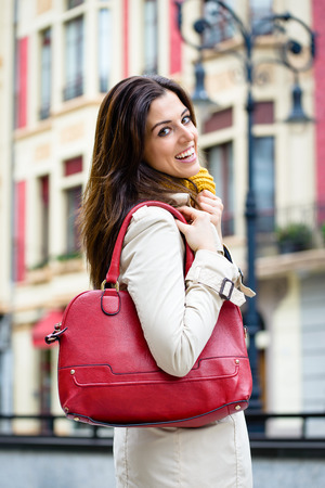 Happy woman walking down the street for shopping at european city wearing raincoat and handbag.  Autumn urban lifestyle and fashion concept. Stock Photo