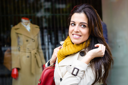 shopwindow: Cheerful brunette woman shopping in autumn. Modern fashion female outside looking shopwindow. Stock Photo