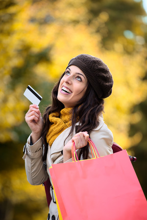 spending money: Fashion trendy woman showing credit card and carrying shopping bags after buying in autumn. Happy caucasian brunette shopper spending money.