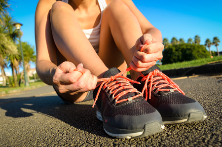 lacing: Female athlete lacing running footwear and getting ready for outdoor workout. Woman exercising in a park on summer. Stock Photo