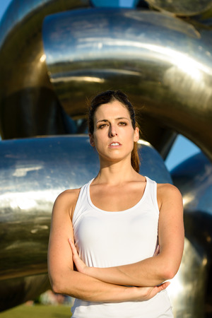 Focused serious female athlete with arms crossed looking motivated. Fitness woman on outdoor summer sunset workout. photo