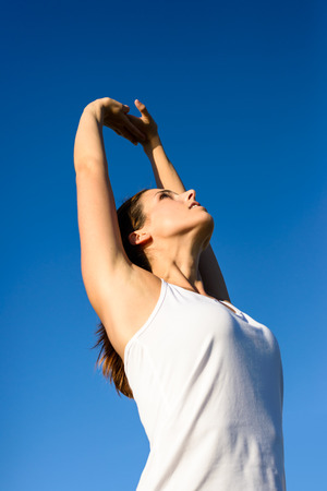 Female athlete stretching arms and back for healthy fitness exercising and relax outdoor. Brunette woman on summer workout doing breathing exercise. photo