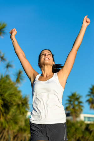 Female athlete running and raising arms for celebrating challenge victory. Woman achieving exercising and sport goals.