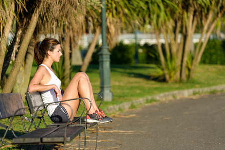 taking a break: Relaxed woman taking a rest after running and fitness exercising outdoor in park. Female athlete on a workout break sitting in a bench.