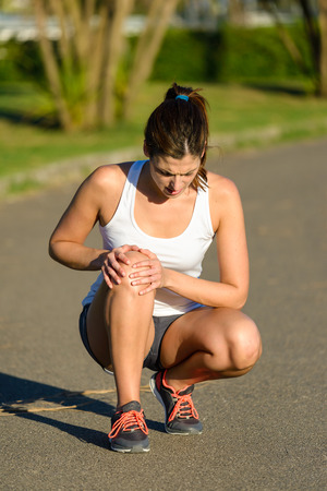 Female caucasian athlete suffering knee joint runner injury.