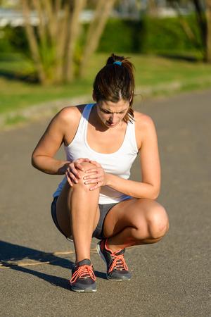 Female caucasian athlete suffering knee joint runner injury.