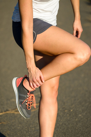 Female caucasian runner suffering ankle sprain sport injury while running.