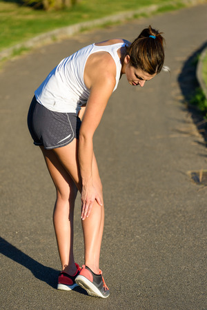 Female caucasian athlete suffering a calf muscle cramp injury while running outdoor in a park.