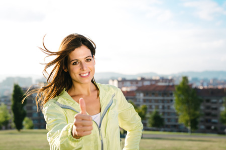 working lifestyle: Sporty urban woman doing success thumbs up gesture after exercising outdoor. Healthy and sport lifestyle concept. Stock Photo