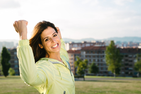 Sporty urban woman celebrating sport and fitness lifestyle success. Happy female athlete raising arms after achieving exercising goals in city park.