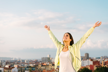 Happy woman celebrating fitness and sport exercising success. Successful female athlete raising arms to the sky on city skiline background. Archivio Fotografico