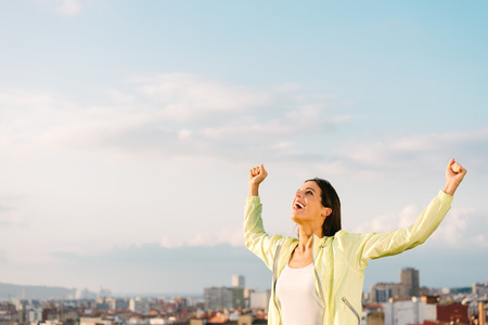 Happy woman celebrating fitness and sport exercising success. Successful female athlete raising arms to the sky on city skiline background. Standard-Bild