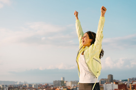 Happy woman celebrating fitness and sport exercising success. Successful female athlete raising arms to the sky on city skyline background.