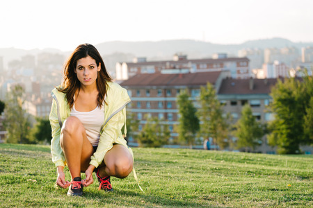 lacing: Woman getting ready for running challenge and sport exercising outdoor in city park on sunset. Female fitness athlete working out for healthy lifestyle.