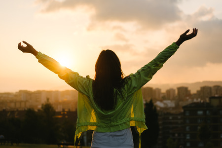 and  celebrate: Back view of a blissful woman celebrating sport and fitness lifestyle success. Female athlete raising arms to the sky after exercising for relax towards beautiful sunset or morning over city skyline. Stock Photo