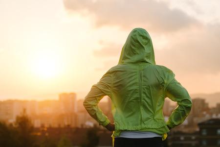 운동 선수의 다시보기는 운동 후 도시의 스카이 라인 일몰을보고. 동기 부여, 스포츠 및 피트니스 라이프 스타일 개념입니다. 스톡 콘텐츠