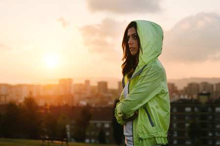 fitness motivation: Serious female athlete crossing arms towards sunrise or sunset over city skyline for sport motivation and fitness lifestyle concept.
