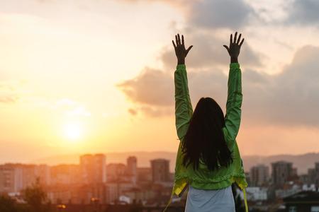 gente saludable: Volver la vista de una mujer feliz celebraci�n de objetivos deportivos y �xito estilo de vida saludable. Atleta de sexo femenino que levanta los brazos al cielo despu�s de hacer ejercicio a hermosa puesta de sol o de la ma�ana sobre el horizonte de la ciudad.