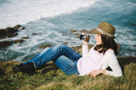 Relaxed hipster woman enjoy the views on vacation travel. Funky girl taking photos towards the sea. photo