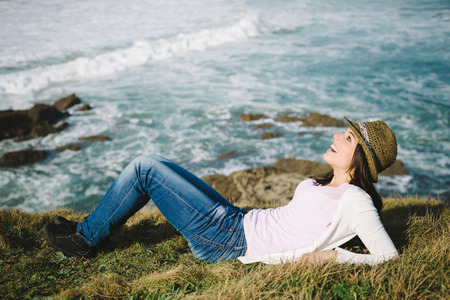 Happy funky woman lying down and enjoying leisure and vacation on coast travel towards the sea. photo