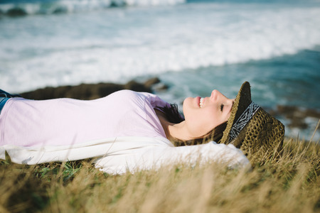 Funky young woman resting and relaxing towards the sea. Cheerful brunette enjoying silence and tranquility. photo