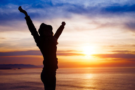 Blissful woman enjoying freedom and happiness on beautiful sunset towards the ocean and sky.