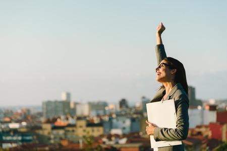 Succès jeune femme d'affaires bras de relevage célébrer entreprise ou la réalisation de l'emploi vers la ville de fond. Professional femme heureuse marcher à l'extérieur. Banque d'images - 35777792