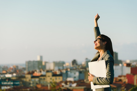 business success: Successful young businesswoman raising arm celebrating business  or job achievement towards city background. Professional happy woman walking outside.
