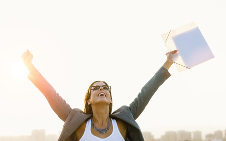 Successful young businesswoman with arms up celebrating business  or job success towards city skyline on sunset or sunrise. Professional happy woman outside.