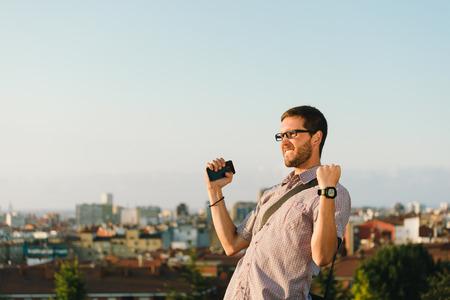 gente celebrando: Exitoso hombre ocasional profesional haciendo un gesto hacia la ciudad. Empresario goza de �xito en el trabajo. Foto de archivo