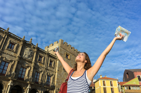 outstretching: Happy woman on summer vacation travel through Spain having fun while visiting typical spanish landmarks.  Female tourist raising arms and holding tourism guide map and camera. Gijon, Asturias, Spain. Stock Photo