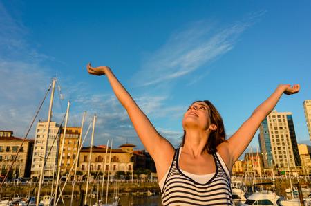 blissful: Joyful woman enjoying european summer travel to Gijon, Asturias, Spain. Blissful tourist raising arms.