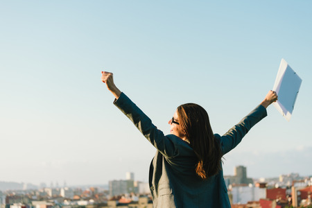 Successful young businesswoman with arms up celebrating business  or job success towards city skyline. Professional happy woman outside.