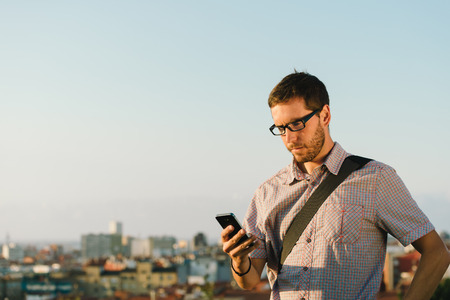 Professional casual man messaging or checking his smartphone against city background.
