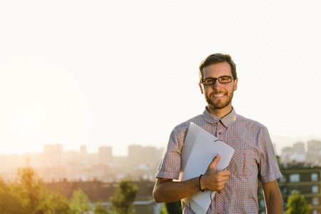 Successful professional casual man walking outside against city background. Happy smart looking person holding folder and smiling. Stock Photo - 35792338