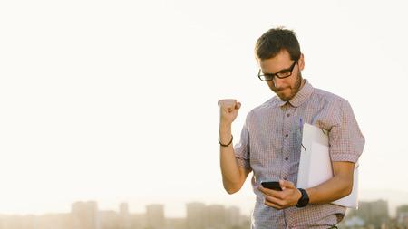 gente exitosa: Hombre de éxito profesional informal gesticulando y revisar los mensajes de teléfonos celulares hacia horizonte de la ciudad. Empresario goza de éxito en el trabajo.