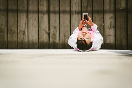 active lifestyle: Cheerful female athlete with smartphone and headphones view from above. Asian sporty woman taking a work out rest. Stock Photo