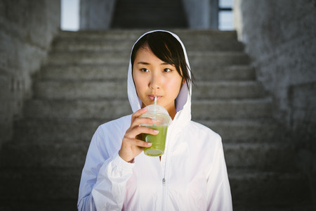 woman outdoor: Asian female fitness athlete drinking green vegetable detox smoothie. Sport diet and nutrition concept. Healthy woman portrait.