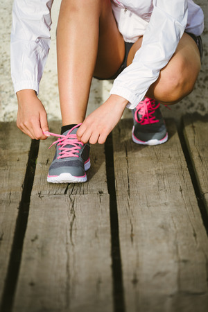 lace up: Female caucasian athlete getting ready for running training. Woman tying sport footwear laces. Sport and healthy lifestyle concept.