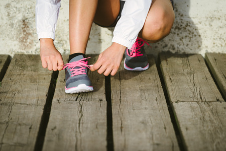 'getting ready': Female caucasian athlete getting ready for running training. Woman tying sport footwear laces. Sport and healthy lifestyle concept.