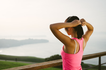 'getting ready': Female athlete getting ready for sport and training. Rear view sporty woman looking the sea. Stock Photo